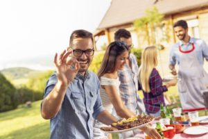 Man with dental implants at barbeque
