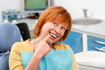 Senior woman pointing to new denture