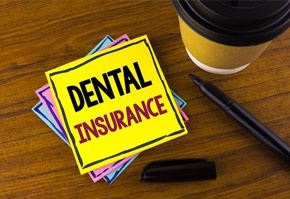 Dental insurance on yellow post it note next to coffee cup