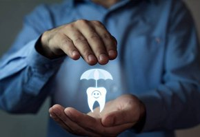 Man's hands holding animated tooth under umbrella