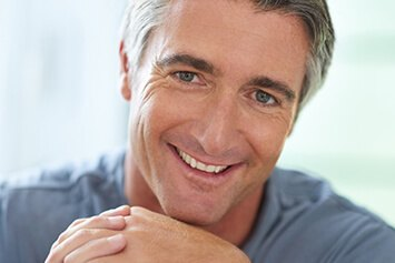 Male in his late 40's wearing a grey shirt smiling